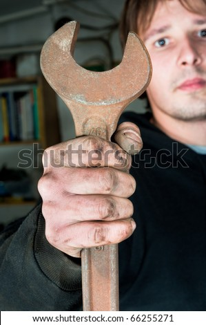 Worker holding large open-end wrench - stock photo