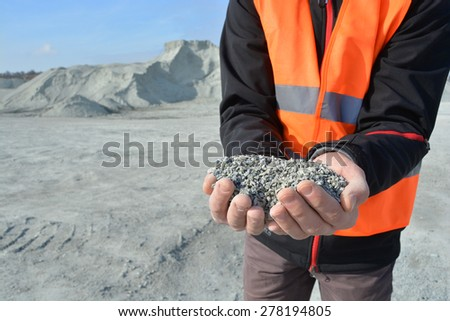 Worker holding pebbles in hands and quarry in background