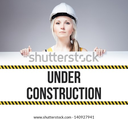 Worker holding under construction sign placed on information board - stock photo