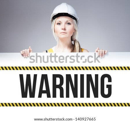 Worker holding warning sign placed on information board - stock photo