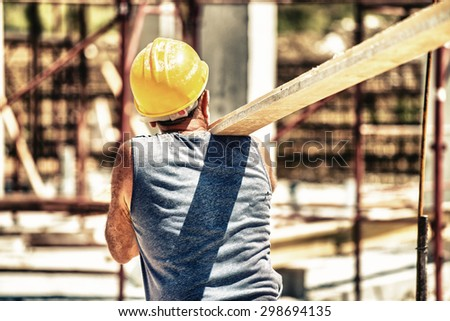 Worker in a construction site transporting a wooden bar. - stock photo