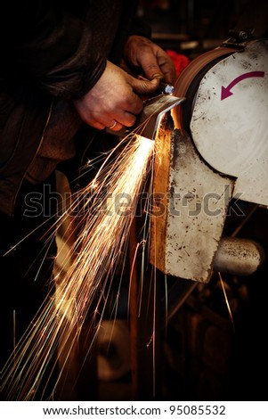 Worker in a factory keeping a metal plate in his hands and grinding it on grinder, causing many sparks - stock photo