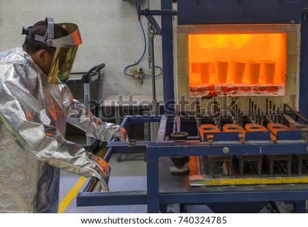 Worker in a fusion and oxidation of steel at high pressure and temperature. Cups filled with bright gold, melted in an industrial stove. Metallurgical production of steel, bronze, metal