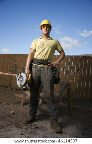 Worker in a hardhat and safety glasses stands at a construction site with a hand on his hip. He holds a circular saw with the other hand. Vertical shot. - stock photo