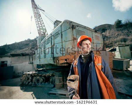 worker in a helmet with a wrench in his hand standing near a construction crane lifting - stock photo