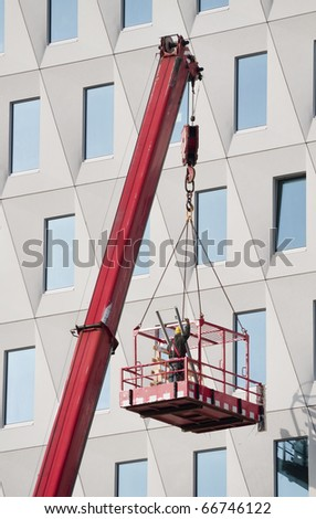 Worker in a hoisted platform  wearing safety harness gives a hand signal to the crane driver - stock photo