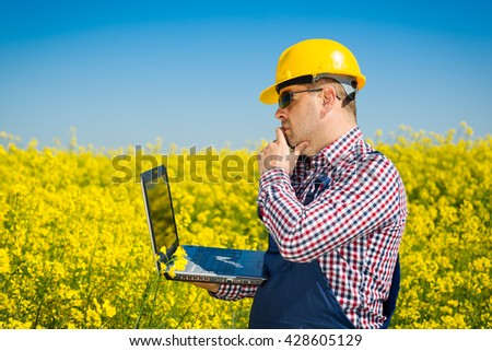 Worker in a rapeseed field doing inspection for biodiesel production - stock photo