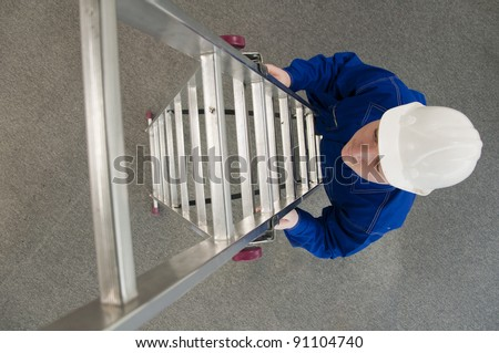 worker in a white helmet, enters the ladder - stock photo