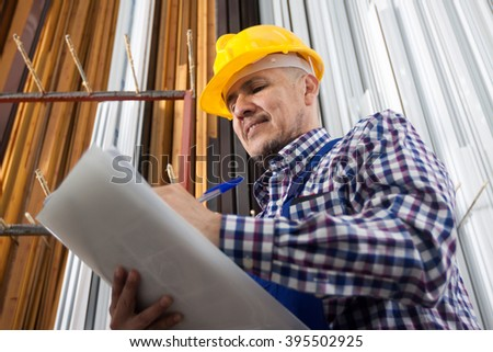 worker in a yellow hard hat taking notes - stock photo