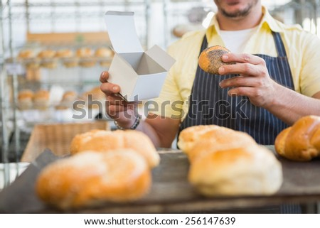 Worker in apron holding box and bread at the bakery - stock photo