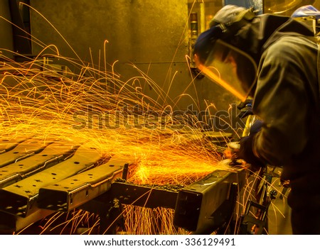 worker in automotive industry movement work grinding parts with sparks - stock photo