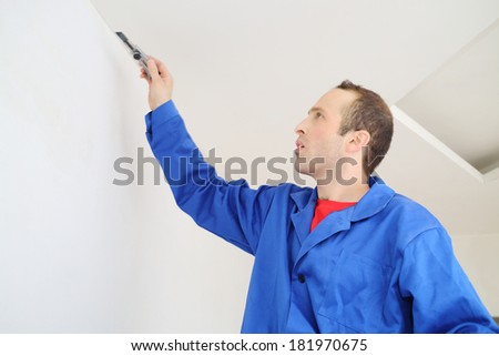 Worker in blue clothes works by building knife in new apartment - stock photo