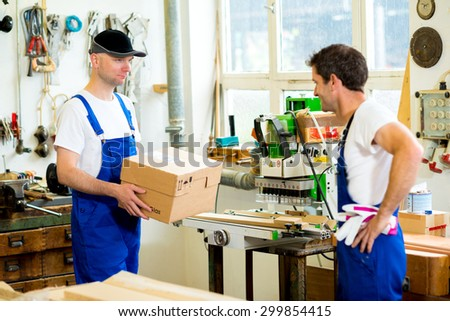 worker in blue dungarees in a carpenter's workshop - stock photo
