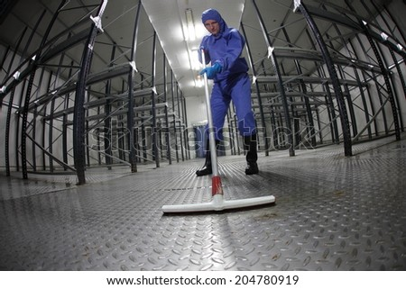 worker in blue, protective  uniform cleaning floor in empty storehouse - fish eye lens - stock photo