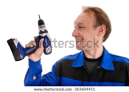 Worker in blue uniform looking at battery screwdriver in his hand, isolated on white