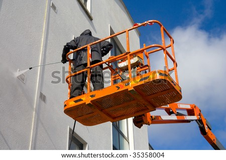 Worker in cherry-piker Washing A Wall - stock photo