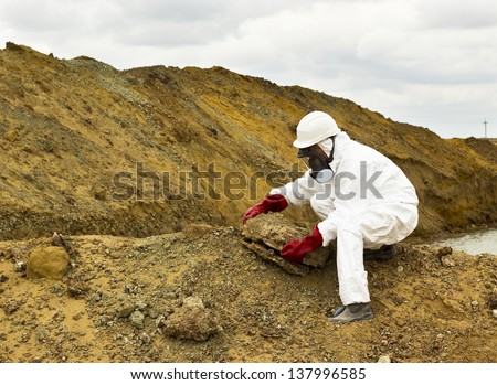 worker in coveralls and mask takes a sample of the soil in the contaminated area - stock photo