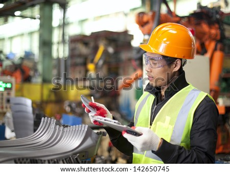 worker in factory checking quality of metals - stock photo