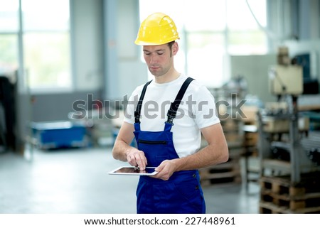 worker in factory using tablet pc - stock photo