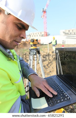 Worker in front of a laptop computer on site - stock photo