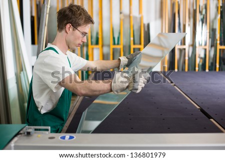 Worker in glazier's workshop or glass warehouse handling glass