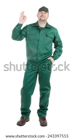 Worker in green with ok sign. Isolated on a white background.
