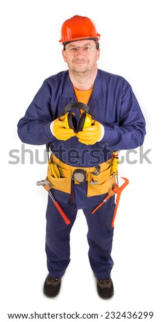 Worker in hard hat holding ear muffs. Whole background. - stock photo