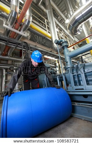 Worker in helmet and uniform, inside plant dealing with plastic barrel - stock photo
