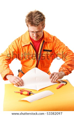 worker in orange work wear carefully folds a paper sheet, isolated on white - stock photo