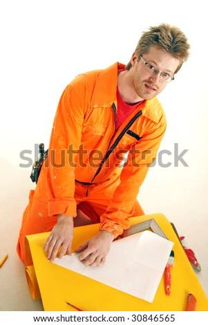 worker in orange workwear folds a paper sheet - stock photo