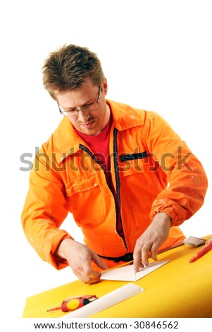 worker in orange workwear folds a paper sheet, isolated on white - stock photo