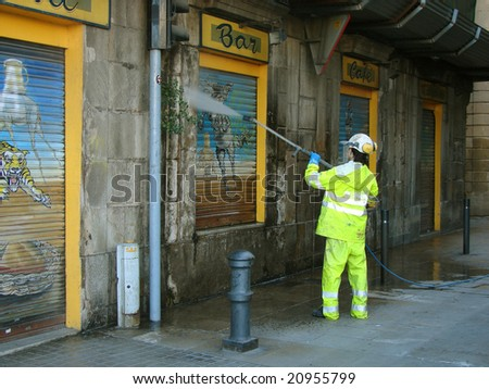 worker in overalls washing a wall