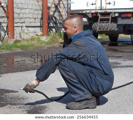 Worker in overalls watering the paved area with water