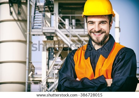 Worker in protective uniform and protective helmet in front of oil plant - toned image, retro film filtered in instagram style - stock photo
