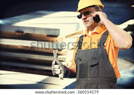 worker in protective uniform and smart phone in front of sheet tin metal in production hall - toned image, retro film filtered in instagram style - stock photo