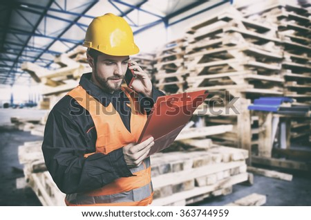 Worker in protective uniform in front of wooden pallets - toned image, retro film filtered in instagram style - stock photo
