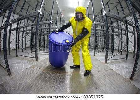 Worker in protective uniform,mask,gloves and boots rolling barrel of chemicals in empty storehouse - fish eye lens  - stock photo
