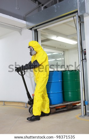 Worker in protective uniform,mask,gloves and boots  transport barrels of chemicals on forklift