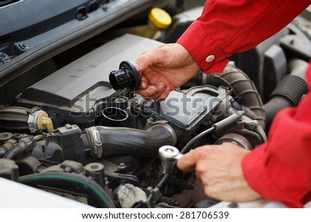 Worker in red overalls checking the oil on car car engine