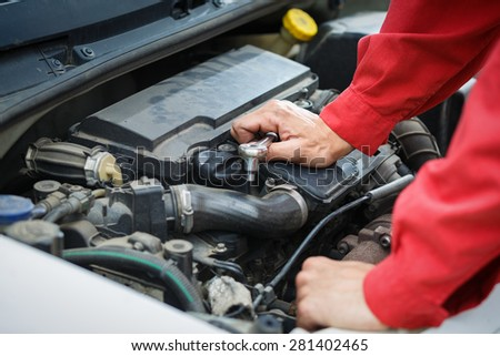 Worker in red overalls repairing the car engine. Detail of engine and hands