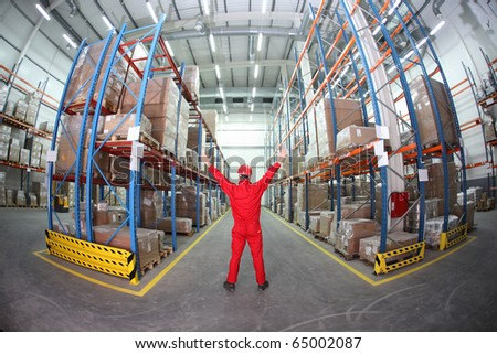 worker in red uniform raising hands in the middle of warehouse - stock photo