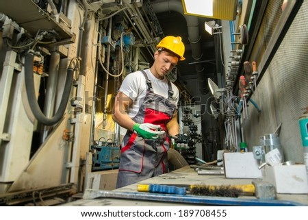 Worker in safety hat in machinery room on a factory - stock photo