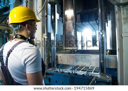 Worker in safety hat near machine on a factory - stock photo