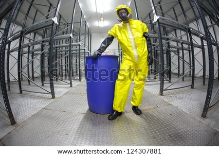 worker in safety - protective uniform,standing at blue barrel - portrait - stock photo