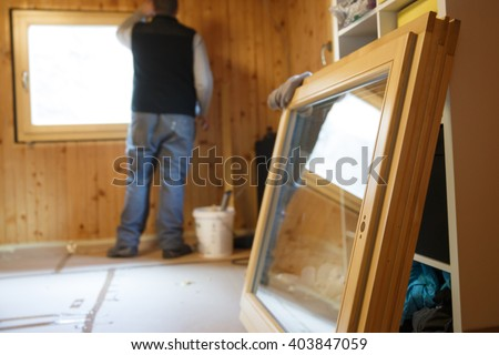 Worker in the background installing new, three pane wooden windows in an old wooden house, with a new window in the foreground. Home renovation, sustainable living, energy efficiency concept.  - stock photo