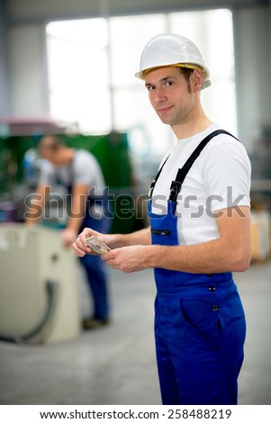 worker in the factory with his wages - stock photo