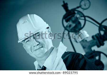 Worker in uniform and helmet on of background the valves, piping and sky. Look into the camera. Toned. - stock photo