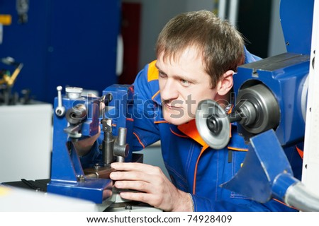 worker in uniform and protective glasses working on sharpening machine tool - stock photo