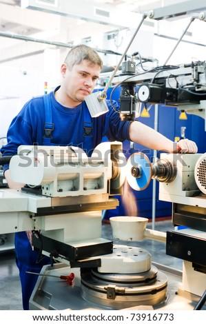 worker in uniform working on sharpening machine tool - stock photo