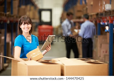 Worker In Warehouse Checking Boxes Using Digital Tablet - stock photo